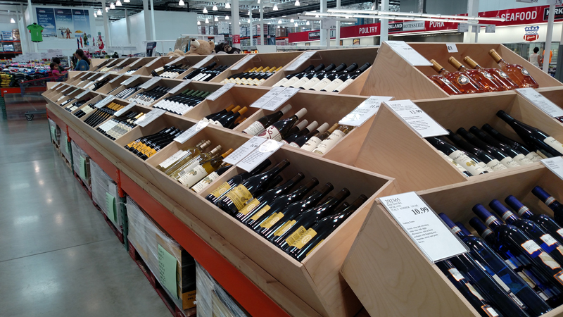 The higher-end wines at Costco are displayed in wooden bins.